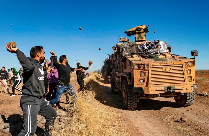 Kurdish demonstrators hurl rocks at a Turkish military vehicle