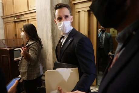 Trump loyalist Josh Hawley ignores impeachment trial evidence by sitting in gallery to review paperwork